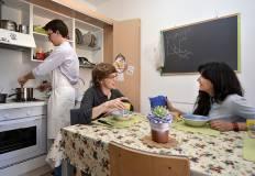 Un ragazzo e due ragazze nella cucina dello Studentato