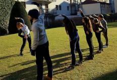 Ragazzi e ragazze sul prato fanno esercizi con l'istruttrice.