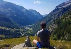 Un ragazzo seduto guarda le montagne e la valle